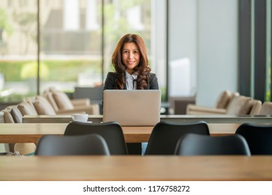 Portrait of a cheerful asian businesswoman sitting at the table in office and looking at camera.