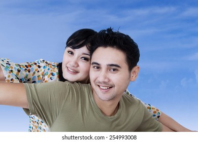 Portrait of cheerful asian couple playing together under blue sky
