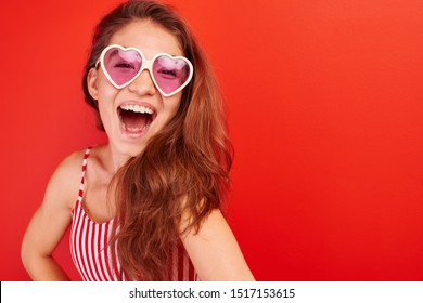 Portrait of cheerful asian kazakh young woman in summer glasses dressed casual smiling joyfully isolated on red with copy space