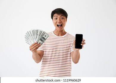Portrait of a cheerful asian man holding money banknotes and showing blank screen mobile phone isolated over white background