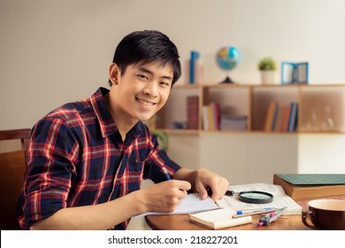 Portrait of cheerful Asian student doing homework