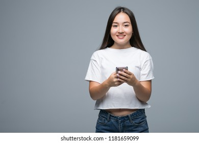 Portrait of a cheerful asian woman holding mobile phone and looking at camera isolated over gray background