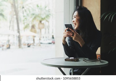 Portrait of a cheerful asian woman looking at the street while sitting in a coffee shop with a mobile phone in her hands. Business woman happy to read good news on a smartphone form business partners