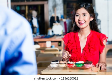 Portrait of a cheerful Asian woman ordering cupcakes behind the counter in a cool coffee shop with various delicious confections