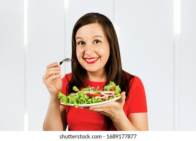 Portrait of a cheerful athletic woman eating healthy salad. Concept of losing weight, sports and healthy eating.