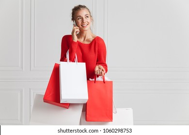 Portrait of cheerful attractive girl with charming smile. Joyous blonde holding red and white shopping packets in hands and speaking on smartphone. Copy space in right side