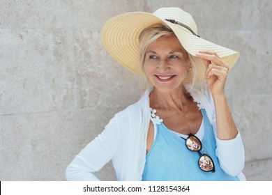 Portrait of cheerful attractive mature blonde woman wearing summer hat