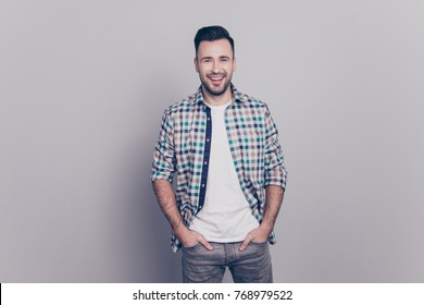 Portrait of cheerful, attractive, smiling man holding hands in pocket of jeans looking at camera standing over grey background