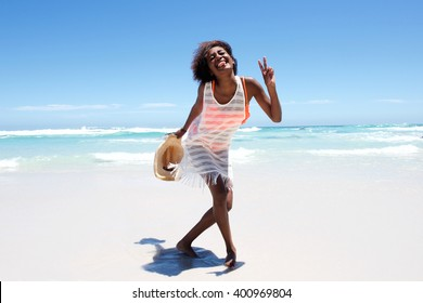 Portrait of cheerful attractive young african woman enjoying walk on beach