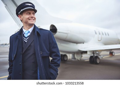 Portrait of cheerful aviator keeping hands in pocket while standing opposite aircraft. Crew concept
