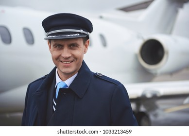 Portrait of cheerful aviator locating near aircraft. He looking at camera. Positive concept