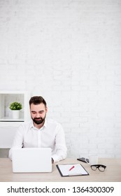 portrait of cheerful bearded businessman using laptop in office - copy space over white brick wall background