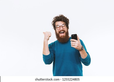 Portrait of cheerful bearded hipster man holding phone and showing thumbs up or pointing away over white background
