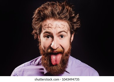 Portrait of a cheerful bearded man with hair standing up on end against a black background. with inscription CRAZY on the forehead. close up