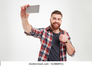 Portrait of a cheerful bearded man taking selfie and showing thumbs up gesture over white background