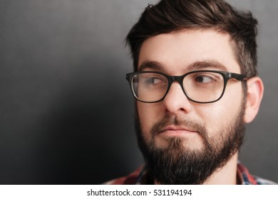 Portrait of cheerful bearded man wearing glasses standing over chalkboard. Look aside.