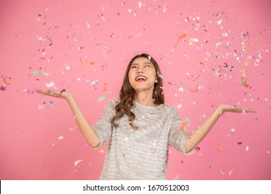 Portrait of a cheerful beautiful Asian womanl wearing dress standing standing under confetti rain and celebrating isolated over pink background