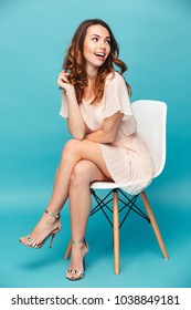 Portrait of a cheerful beautiful girl wearing dress sitting on a chair and looking away isolated over blue background