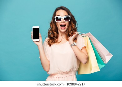 Portrait of a cheerful beautiful girl wearing dress and sunglasses holding shopping bags and mobile phone isolated over blue background