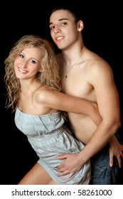 Portrait of cheerful beautiful young couple. Isolated on black