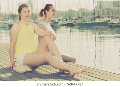 Portrait of cheerful belorusian young traveling girls sitting on promenade  sea