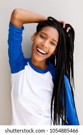 Portrait of cheerful black girl with braided hair smiling against a wall