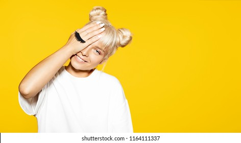 Portrait of cheerful blonde hipster girl going crazy and smiling. Cute lady posing with fake eyelash on yellow background. Concept of emotions.