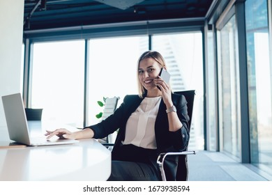 Portrait of cheerful blonde woman entrepreneur in formal wear satisfied with good mobile phone conversation during working process,smiling female manager typing on laptop computer talking on cellular