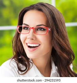 Portrait of cheerful brunette businesswoman in glasses