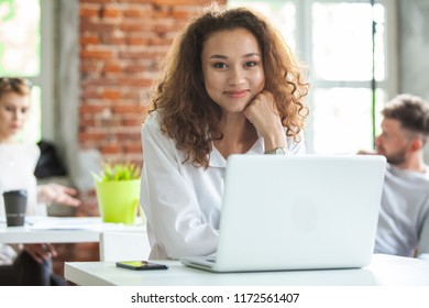 Portrait of cheerful business African-American lady working on laptop