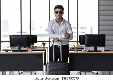 Portrait of cheerful business man holding passport and luggage in workplace of office. Summer vacations concept.