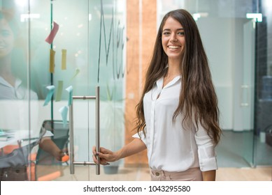 Portrait of cheerful business woman entering meeting room.
