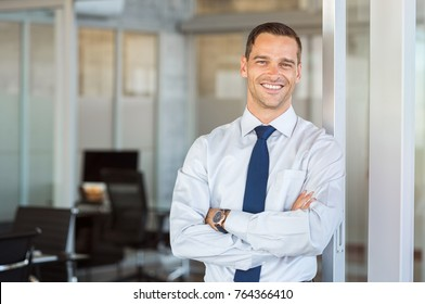 Portrait of cheerful businessman with arms folded standing in conference room. Happy young business man in shirt looking at camera. Portrait of a smiling businessman in modern office with copy space.