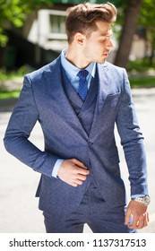 Portrait of a cheerful businessman in blue suit, summer street outdoors