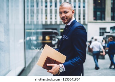 Portrait of cheerful businessman dressed in stylish formal wear holding folder with financial documents in hand and smiling at camera strolling in urban setting in modern city during work break