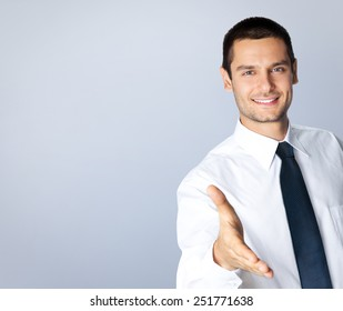Portrait of cheerful businessman giving hand for handshake, with blank copyspace area for text or slogan, against grey background