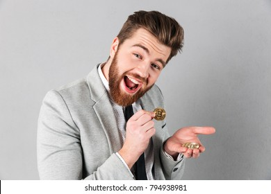 Portrait of a cheerful businessman showing golden bitcoins in his hands isolated over gray background
