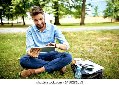 Portrait of cheerful businessman sitting in park during lunch and using tablet