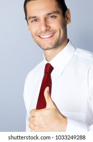 Portrait of cheerful businessman with thumbs up gesture, against grey background