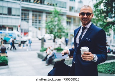 Portrait of cheerful businessman in trendy sunglasses satisfied with personal shopper service enjoying buying, smiling entrepreneur spending free time in good mood having cup of coffee to go