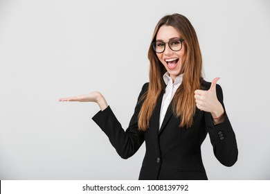 Portrait of a cheerful businesswoman dressed in suit showing thumbs up and holding copy space on her palm isolated over gray background