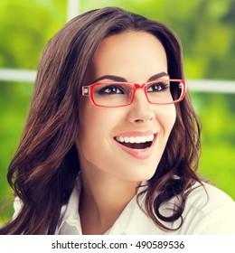 Portrait of cheerful businesswoman in glasses. Caucasian brunette model in business concept shoot.