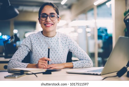 Portrait of cheerful businesswoman satisfied with occupation sitting at desktop in office with modern technologies,smiling female designer happy about accomplished creative project looking at camera
