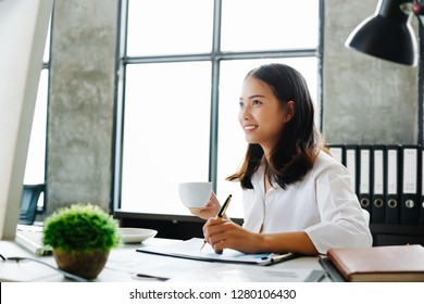 Portrait of a cheerful businesswoman sitting at the table in office, Business Woman using computer.