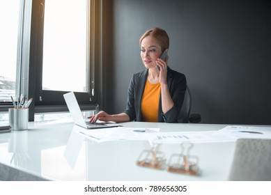 Portrait of cheerful businesswoman speaking by mobile while noting in notebook computer. Profession and conversation concept. Low angle
