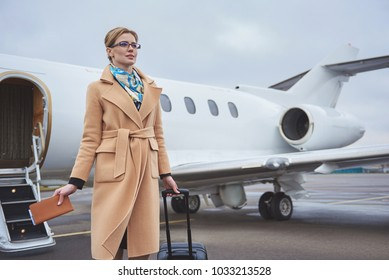 Portrait of cheerful businesswoman standing at airfield opposite plane. Arrival concept