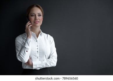 Portrait of cheerful businesswoman telling by phone at work. Conversation and career concept. Copy space