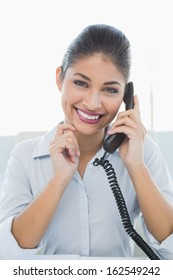 Portrait of a cheerful businesswoman using telephone against white background
