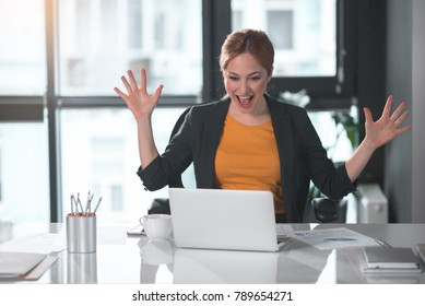 Portrait of cheerful businesswoman waving arms while looking at notebook computer. Career and enthusiasm concept