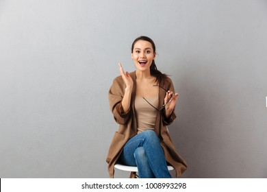 Portrait of a cheerful casual asian woman sitting on a chair and celebrating over gray background